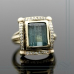 green tourmaline and diamond halo ring in 14k yellow gold